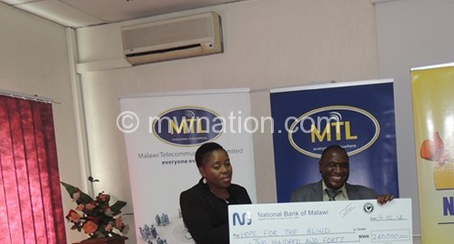 Das (R) handing over the cheque to Bwande