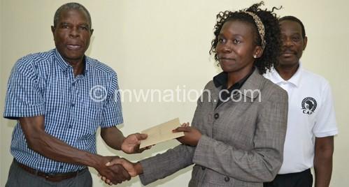 Msiska receives her badge from Kalombo