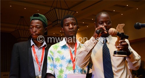 Thom (R) and other Fikisa members give their acceptance speech