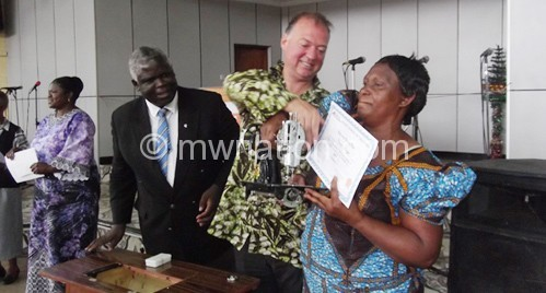 Buydens (C) presents a sewing machine to one of the  beneficiaries