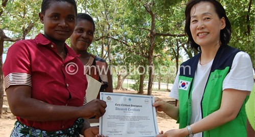 One caregiver (L) receiving a certificate from IL