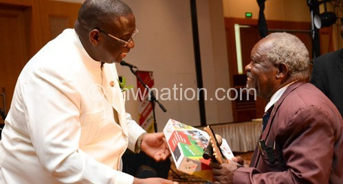 Vice President Khumbo Kachali presents the Lifetime Achievers' award to Che chamba at the MAM Music awards in Lilongwe on Friday