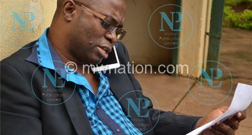 Raphael Kasambara reading his charge sheet at his home in Area 10 minutes before he was rearested.