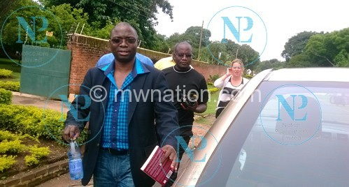 Raphael Kasambara  leaving his home for  National Police Headquoters. In the background a police officer carrying a camera the police confiscated from NPL photojournalist.