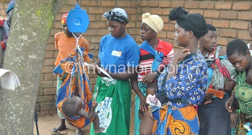 Women weigh their children on a scale at the clinic