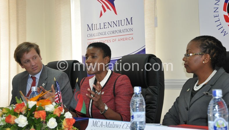 Butts (C) addressing journalists flanked by MCC resident country director Oliver Pierson (L) and Banda (R)