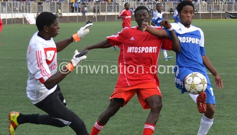 Bullets goalkeeper Owen Chaima (L) and Pilirani Zonde (C) try to stop Nomads' Kondwani Kumwenda (R) during the game