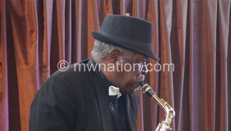 Chechamba performing with a saxophone