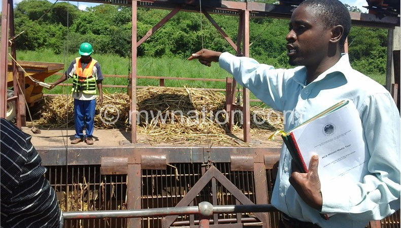 Chilimampunga pointing at weeds that affect power generation at Nkula