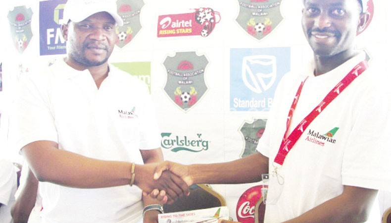Ndaombwa (R) makes a symbolic presentation of the tickets to Nyirenda
