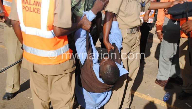 Police carry an injured person during the Thyolo fracas