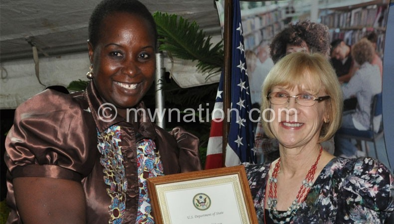 Kabwila (L) receives a certificate from Jackson