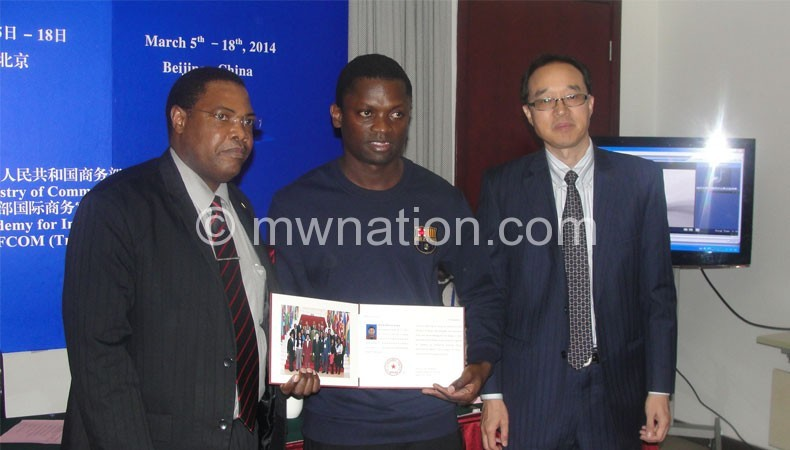 Kaminjolo (C) displays a certificate of attendance flanked by Chinese and Malawi Government officials