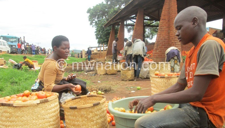 A woman and her son sort tomatoes at Jenda Market