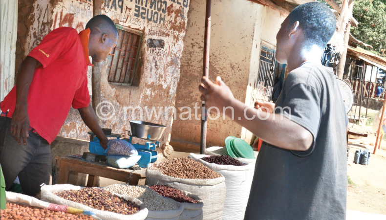A vendor (in red T-Shirt) selling unprocessed legumes in Blantyre