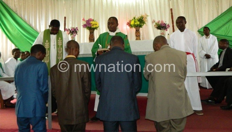 An Anglican priest blesses part of Claim team