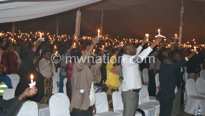 Patrons hold out the candles during the service
