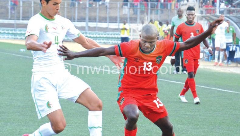 Frank Banda beats Algeria defender Mandi Aissa (L)
