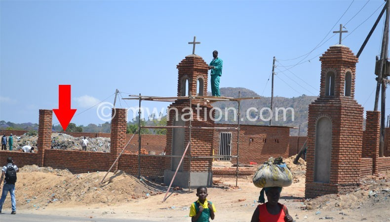 Part of the church being constructed with the arrow pointing to a tomb