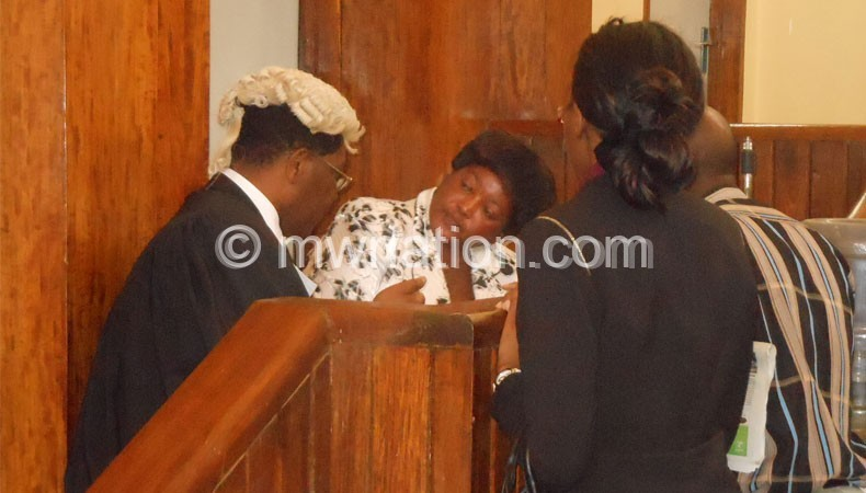 Treza Senzani (In White) consulting with her lawyer, Mhura