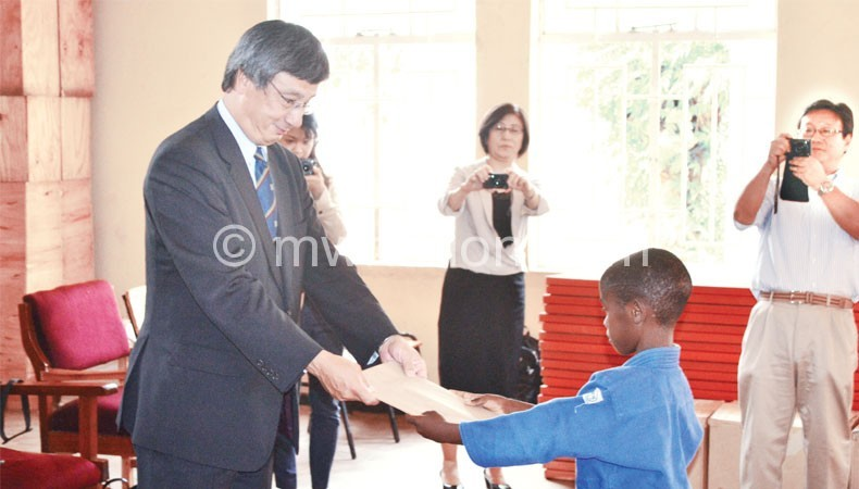 Nishioka (L) receives a gift from a judo athlete in Malawi