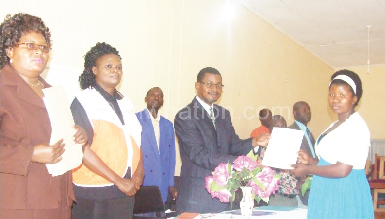 Bamusi (L) Movete in suit presenting certificate to one of graduates