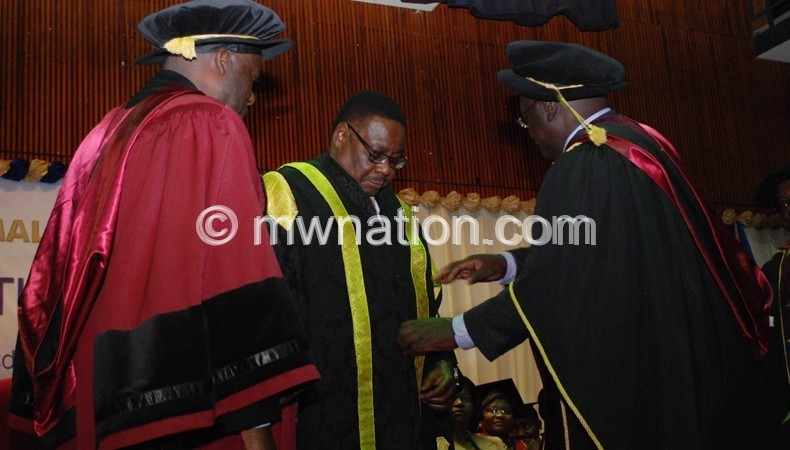 UNIMA Registra and vice Chancellor confering president Peter Mutharika as the University's new Chancellor at Chancellor colloge on Wednesday.Pic by Govati Nyirenda. Mana