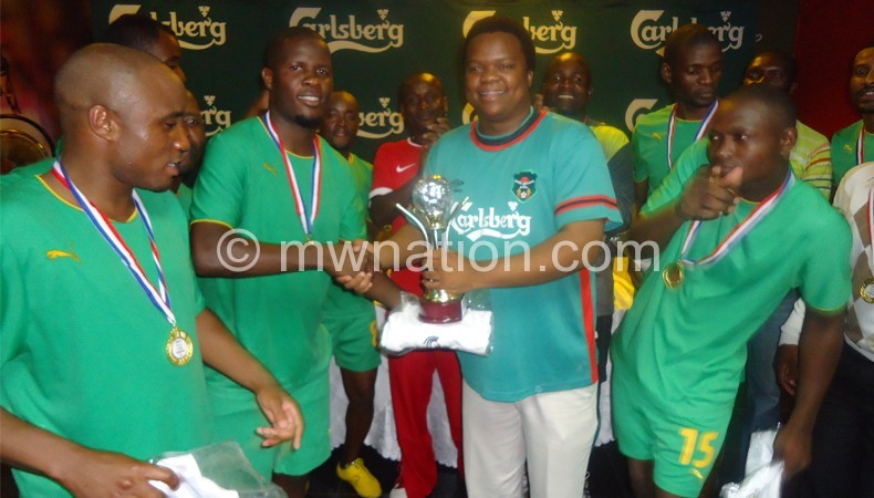 Chirwa (R) presents trophy to Munthali as his team mates look on