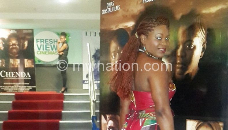Suya poses on a poster of the film during the launch in Zambia