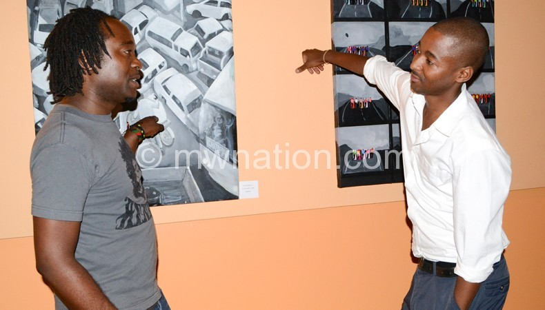 Kambalu (L) showing a patron his art during an exhibition