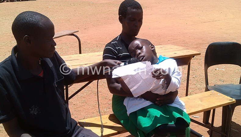 Lekeleni recites a poem while sitting on her mother's lap