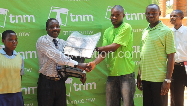 Francis Chilowa [TNM winner] presenting one of computers to the headmaster of Chintheche CDSS Eston Kaponde and looking on is TNM Head of region North Richard Kwatiwani [in green golf shirt].