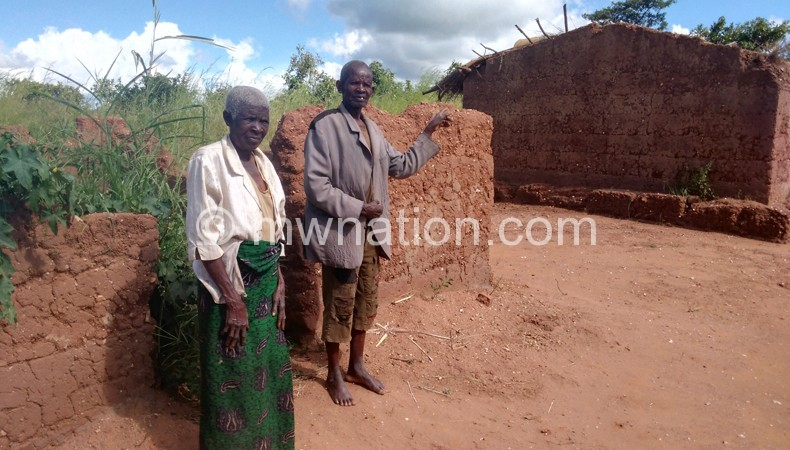 Some of the displaced residents standing next to their dilapidated home