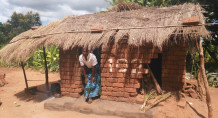 A woman walks out of her dilapidated home