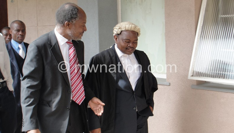 Chilumpha (L) and Kaphale, then his legal counsel, share notes after a court appearance