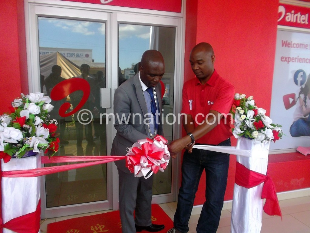 Maunde (L) cutting the ribbon assisted by Kamoto marking the opening of the new shop in Zomba