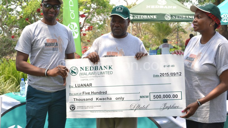 Nedbank Malawi MD Paul Guta (L) poses with a dummy cheque with Kanyama-Phiri (C) and Mbuyane-Mokone