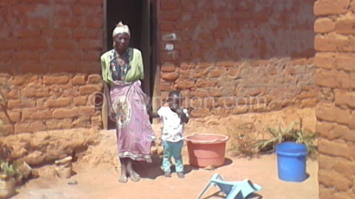 Nkhwazi with her great grandchild outside her home