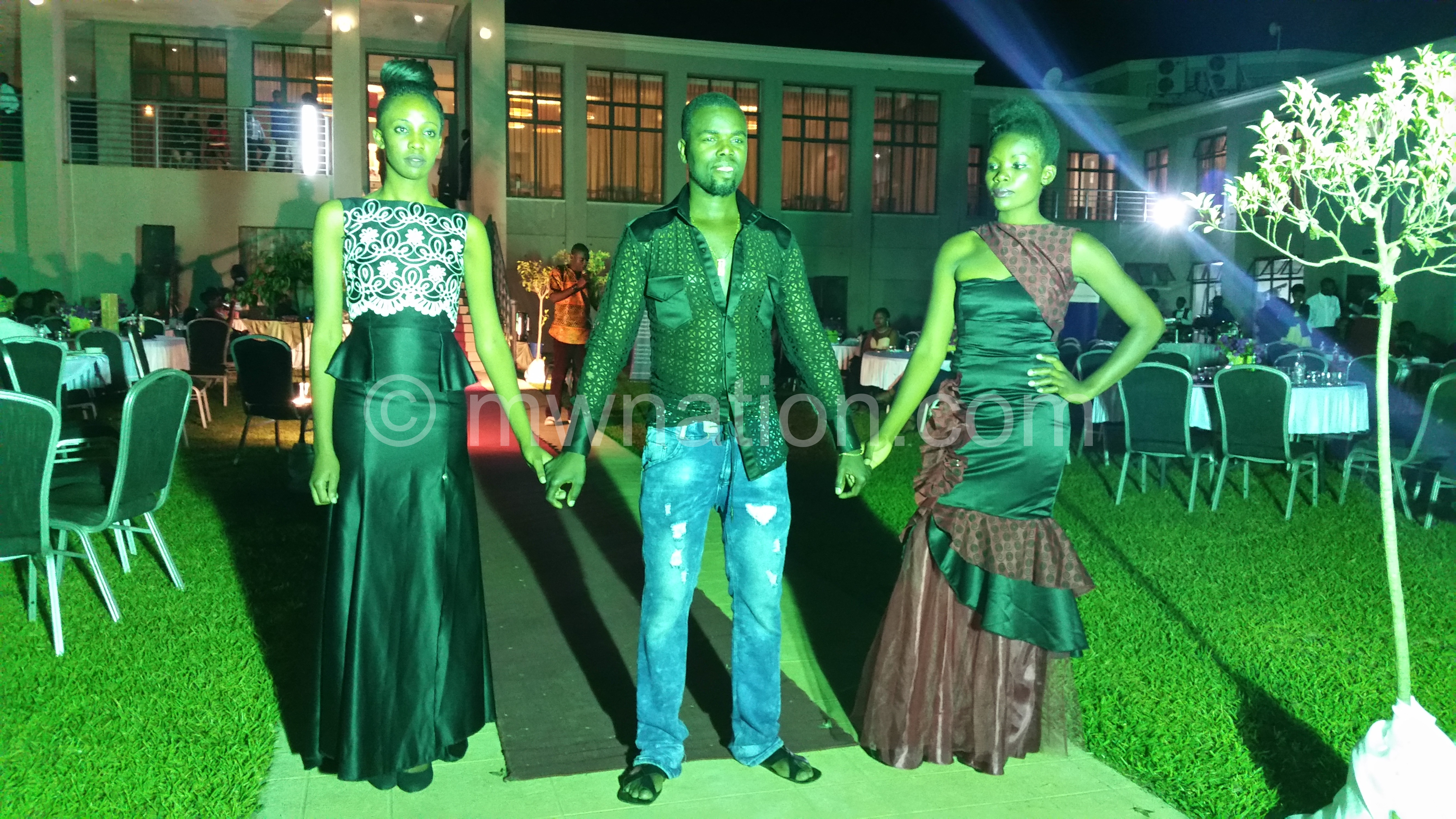 Clemoh Sato (C) poses with models wearing his designs at the Mzuzu Fashion Week