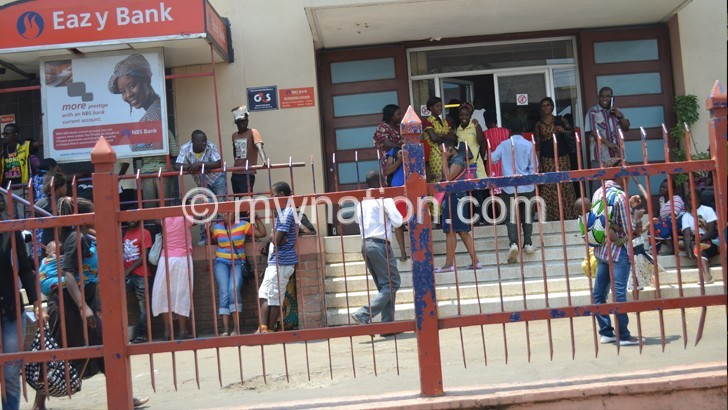 Hopeless: Some of the frustrated customers outside  the bank's Limbe Branch