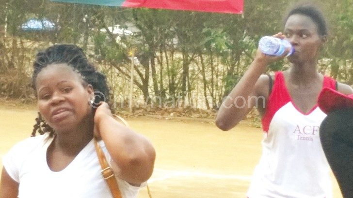 Luhanga (R) cools off with a bottle of water after  beating Matola-Mlomba (L)