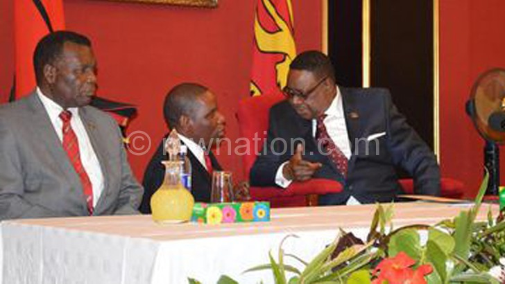 Mutharika confers with Mwanamvekha during the briefing as Minister of Foreign Affairs and International Cooperation George Chaponda looks on