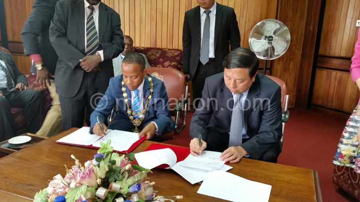 Chalamanda and Guan signing the MOU