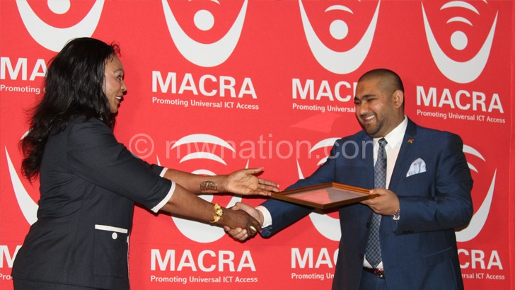 Here you are: Macra board chairperson Alisha Makawa presents the licence to Sattar (R) on Monday