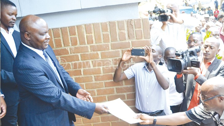 Mambala (R) hands over a copy of their statement to Jappie Mhango