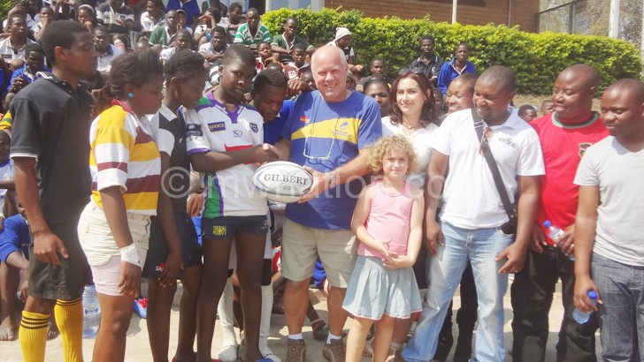 Colony Club's Loudon presents rugby ball to  Mwale as others look on