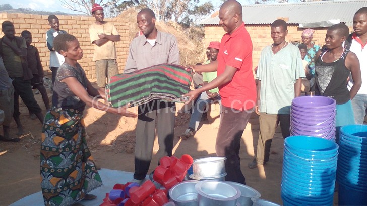 A beneficary receiving a blanket from Masingati(in red)
