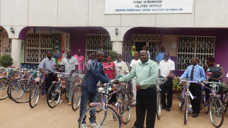 Banda handing over a bicycle to a volunteer