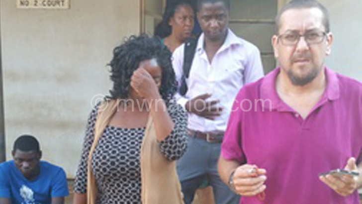 Ndovi (hiding her face) leaves court with her husband (R) and other well-wishers