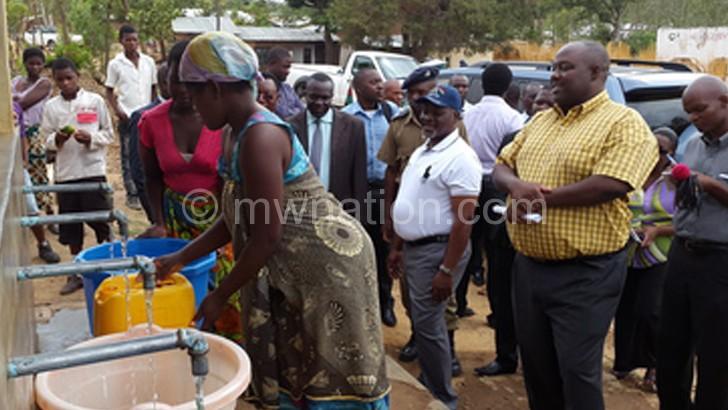 Chiyembekeza (in cap) and BWB acting chief executive Henry Bakuwa watching a woman drawing water